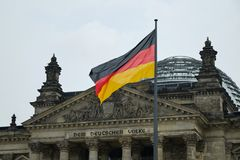 Reichstag building and German Unity Flag. Berlin, Germany - April 14, 2018: Fronton with columns and dome of Reichstag building with German Unity Flag on the Stock Photos