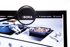 Berlin, Germany - April 1, 2019: Illustrative Editorial of Bora official website homepage under magnifying glass. Concept Bora logo visible on screen royalty free stock photography
