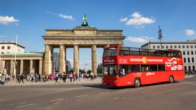 Tourist bus Brandenburger Tor Berlin Germany. BERLIN, GERMANY - APRIL 28, 2018: Red tourist bus driving past the famous German landmark and national symbol royalty free stock image