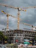 High cranes against cloudy sky. Berlin, Germany - August 20, 2018: Cranes on construction site against cloudy sky royalty free stock photo