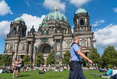 People relax in sun on lawn as tourists take selfie and police pass Berlin Cathedral. BERLIN, GERMANY - AUGUST 28, 2017; People relax in sun on lawn as tourists Royalty Free Stock Image