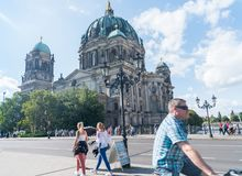 Tourists pass on street outside historic Berlin Cathedral on one end Museum Island example of Baroque architecture Royalty Free Stock Photography