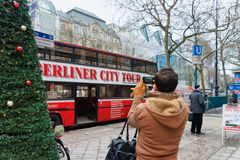 Man taking photos of City tour touristic bus on his mobile phone in Berlin, Germany. Berlin, Germany - December 11, 2017: Man taking photos of City tour stock photography