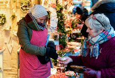 Berlin, Germany - December 8, 2017: Trader giving cash change to a customer buying Christmas Decorations at Night Christmas Market. At Gendarmenmarkt in Winter stock image
