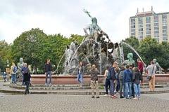 berlin germany En blodstockning av turister om Neptunspringbrunnen arkivbilder