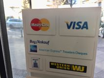Brands of payment systems. Berlin, Germany - February 2, 2018: Logos of Mastercard, Visa, American Express Travelers Cheques, Western Union on a window sticker royalty free stock photo