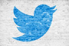Twitter social media blue bird sign logo symbol in minimalist design painted over white brick wall background. BERLIN, GERMANY - JAN 20 2019: Twitter social stock photos