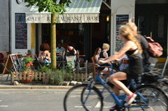 Berlin, Germany - July 2015 - Small trendy street restaurant with tourists cycling royalty free stock photo