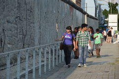 Berlin, Germany - July 2015 - tourists walking next to the Berlin Wall. Asian tourists photographed next to the remnants of the Berlin Wall in the city of Berlin Stock Photos