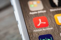 Close up to app on iPhone 7 screen. BERLIN, GERMANY - JUNE 6, 2018: Close up to Aobe Acrobat app on the screen of an iPhone 7 Plus with personalized background Stock Photography