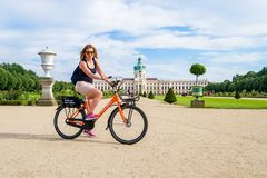 Berlin / Germany - 29 June 2018: Happy girl on rental bicycle, posing in front of Charlottenburg Palace Schloss Charlottenburg stock image