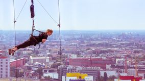 BERLIN, GERMANY-JUNE 18, 2018: a Rope-jumping. Girl waiting for. A jump down on the background of city buildings royalty free stock photo