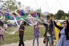 Making Soap Bubbles at Mauerpark. Berlin, Germany - June 10th, 2012: A group of young adults making giant soap bubbles on an early summer Sunday afternoon at Royalty Free Stock Images