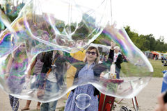 Making Soap Bubbles at Mauerpark. Berlin, Germany - June 10th, 2012: A group of young adults making giant soap bubbles on an early summer Sunday afternoon at Royalty Free Stock Photography