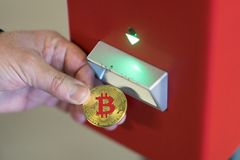 Using bitcoins. Berlin, Germany - March 19, 2018: Human hand inserting a bitcoin into a vending machine. Bitcoins are cryptocurrency and worldwide payment system stock photos