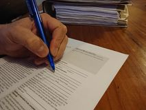 Signing a model release form. Berlin, Germany - March 7, 2018: Left handed man signing a model release form Royalty Free Stock Images