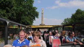City tour, tourists on tour bus without a roof rides on background of monument to the Victory Column. Berlin, Germany 15 May 2018: city tour, tourists on tour stock footage