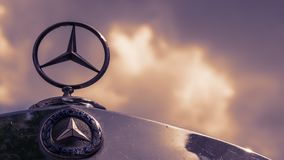 Mercedes Logo And Star On A Mercedes Vintage Car Against A Cloudy Sky royalty free stock photos