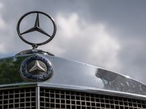 Mercedes Logo And Star On A Mercedes Vintage Car Against A Cloudy Sky stock photos