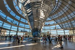 People visit the Reichstag dome in Berlin, Germany. Berlin, Germany - May 27, 2017: People visit the Deutscher Bundestag in Berlin, Germany. It is a glass dome royalty free stock images