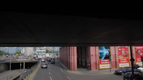 Shots in motion along the city road, cars driving under bridge and stop at the red traffic light. Berlin, Germany 15 May 2018: shots in motion along the city stock video footage