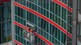 Berlin, Germany - May,2019: Time-lapse motion view window cleaning workflow of modern building on Potsdam square.