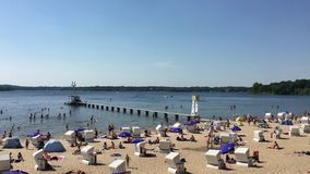 Wide shot of people enjoying and swimming at Wannsee Beach a hot day in Summer stock video footage