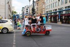 Berlin, Germany, 2014: `Mobile` pub goes along Belina Street. Berlin, Germany, 2014: Six people ride a mobile table-bike along Berlin Street Royalty Free Stock Image