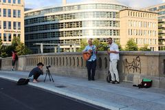 Berlin, Germany: Musicians and girl-photographer on the bridge in Belin. Berlin, Germany: Two musicians are playing on a bridge in Berlin, and a girl-hotographer stock photos