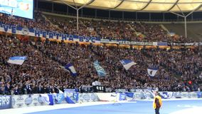 Hertha Berlin ultras perform on tribunes during football game. BERLIN, GERMANY - SEPTEMBER 20, 2017. Hertha BSC Berlin ultras ultra supporters perform on stock footage