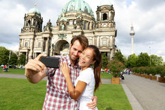 Berlin Germany travel couple selfie self portrait. Happy tourists people in front of Berlin Cathedral / Berliner Dom with Fernsehturm / Berlin TV Tower in the stock photos