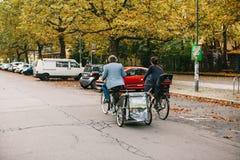 Berlin, le 2 octobre 2017 : Couples inconnus - l'homme et la femme montent ensemble sur des bicyclettes - simples et avec le char Photographie stock libre de droits