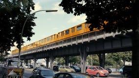 Berlin-Metrozug, der vorbei in sonniges Wetter, Autos unten parken überschreitet stock video footage