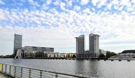 Berlin moderne : beaux bâtiments, sculpture en homme de molécule et ciel nuageux photos stock