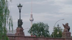 Berlin TV Tower In The Distance At Sunset. Berlin, Moltke Bridge. People Walking By. TV Tower In The Distance. Street Lanterns, Sculptures And Trees. Summer Day stock footage