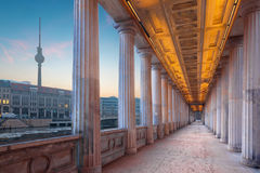 Berlin - The neoclassical porticoes of building of Old National Gallery on the riverside and Fernsehturm tower. In background in morning Royalty Free Stock Images