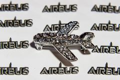 Women`s brooch in the form of an airplane on a background of small lapel pins AIRBUS. Royalty Free Stock Photos