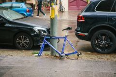 Berlin, October 2, 2017: Blue bicycle attached to street pillar with lock stands without wheels after being stolen in stock photography