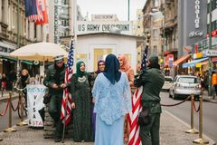 Berlin, October 1, 2017: Positive peaceful cheerful beautiful Arab women in traditional costumes communicate and take. Pictures with American soldiers next to Stock Photo