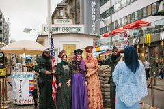 Berlin, October 1, 2017: Positive peaceful cheerful beautiful Arab women in traditional costumes communicate and take. Positive peaceful cheerful beautiful Arab Stock Image