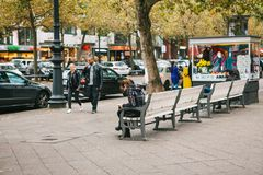 Berlin, October 2, 2017: Young multiethnic couple strolling along Berlin streets next to people sitting on benches royalty free stock photos
