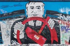 BERLIN - OKTOBER 19, 2016: Konstverk som visar kommunism på Berlin Wall arkivfoton