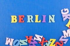 BERLIN ord på blå bakgrund som komponeras från träbokstäver för färgrikt abc-alfabetkvarter, kopieringsutrymme för annonstext Arkivbilder