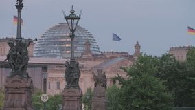 Berlin Reichstag At Sunset. Berlin, Reichstag Building Establishing Shot From An Angle, Street View, EU And German Flags Waving. Street Lanterns With Roman stock video footage