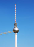 Berlin TV tower. On the background of blue sky, a crane in the side of a tower, height of 368 meters is the tallest building in Germany Stock Photo