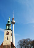 Berlin TV tower and Church of the virgin Mary. Berlin TV tower on the background of blue sky, near the Church of the virgin Mary, the second-oldest parish Church Royalty Free Stock Image