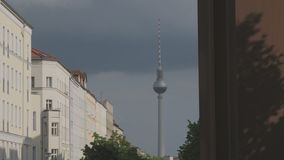 Berlin TV Tower Rising In A Street View. Berlin, TV Tower Street View. Urban Housing Buildings And Wall Memorial Detail On A Summer Day With Rain Clouds And Sun stock footage
