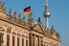 Berlin, tvtorn, historisk byggnad Zeughaus och tysk flagga Royaltyfri Bild
