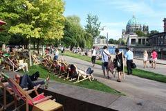 Berlin Tyskland: Folket sitter på deckchairs på gräsmattan nära floden royaltyfri fotografi