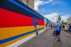 BERLIN TYSKLAND - JUNI 06, 2015: Berlin vägg mycket av graffitis och uttryckt av folk, turists som tar på ett foto Arkivbilder